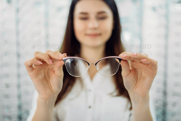 Female customer holds glasses in hand, optic store - Stock Photo - Images