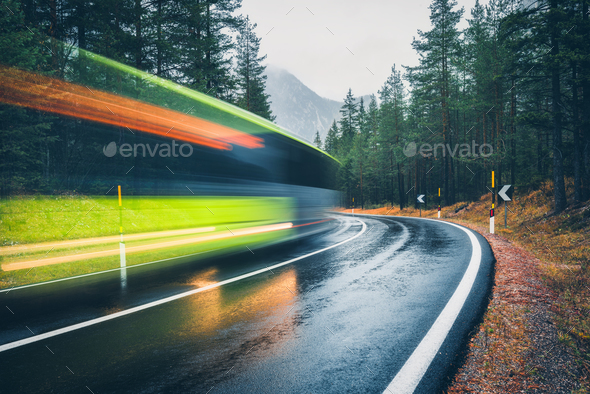 Blurred green bus on the road in autumn forest in rain - Stock Photo - Images