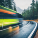 Blurred green bus on the road in autumn forest in rain