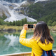 Young woman traveler photographing beautiful landscape with smart phone - PhotoDune Item for Sale