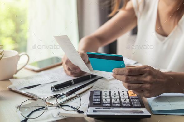 Young woman checking bills, taxes, bank account balance and calculating credit card expenses at home - Stock Photo - Images