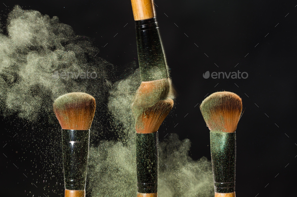 Cosmetics brush and explosion colorful makeup powder background - Stock Photo - Images