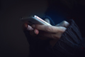 Close up of woman hands in dark sweater hands holding a phone - PhotoDune Item for Sale