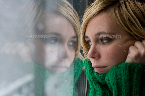 Beautiful blonde woman with sweater in front of a window - Stock Photo - Images