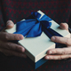 man with black sweater holding a gift with blue ribbon - PhotoDune Item for Sale