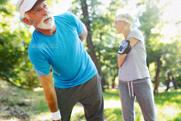 Mature man having a back pain during jogging - Stock Photo - Images