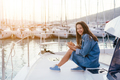 Young beautiful girl is sitting on the deck of a yacht with a smartphone - PhotoDune Item for Sale