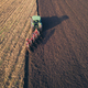 Aerial photo of a tractor ploughing a field in a countryside - PhotoDune Item for Sale