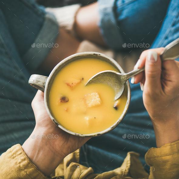 Female keeping mug of warming pumpkin cream soup, square crop - Stock Photo - Images