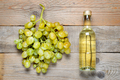 Small bottle of white wine and bunch of grapes on wooden background - PhotoDune Item for Sale
