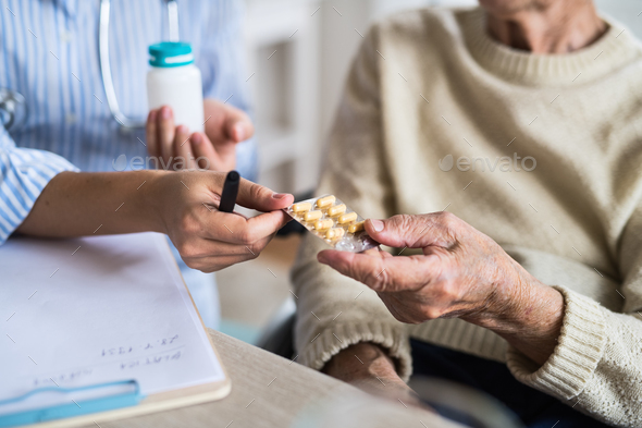 An unrecognizable health visitor explaining a senior woman in wheelchair how to take pills. - Stock Photo - Images