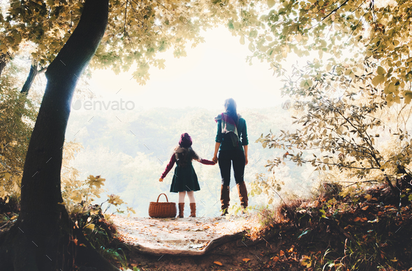 A rear view of mother with a toddler daughter standing in forest in autumn nature. - Stock Photo - Images