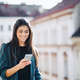 Young businesswoman with smartphone standing on a terrace outside an office in city. - PhotoDune Item for Sale