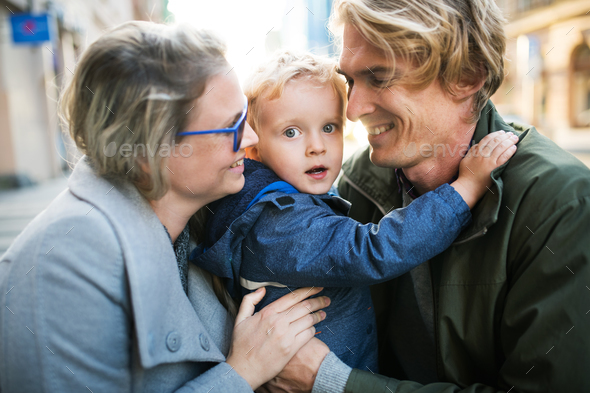 Young parents hugging their toddler son outdoors in city. - Stock Photo - Images