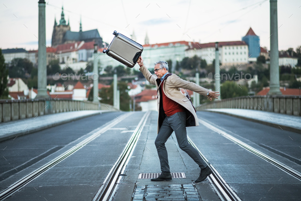 A happy mature businessman with suitcase crossing a road in Prague city. - Stock Photo - Images