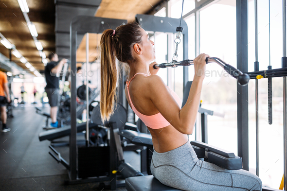 Happy woman exercising on a shoulder press in fitness center - Stock Photo - Images