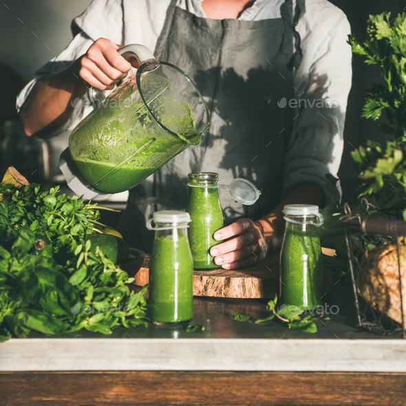 Woman pouring green smoothie from blender to bottle, square crop - Stock Photo - Images