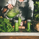 Woman pouring green smoothie from blender to bottle, square crop - PhotoDune Item for Sale