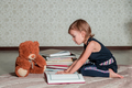 A little girl reading a book sitting on the floor - PhotoDune Item for Sale