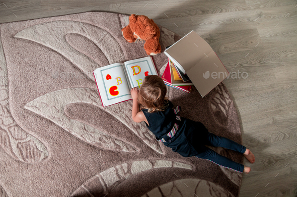 A little girl reading a book sitting on the floor - Stock Photo - Images
