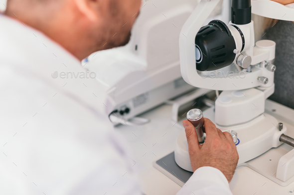 Doctor operating an optical machine. - Stock Photo - Images