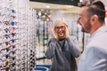 Optician and client choosing glasses together. - PhotoDune Item for Sale