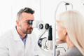 Optician examining his patients eyesight. - PhotoDune Item for Sale