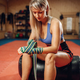 Female kickboxer sitting on punching bag in gym - PhotoDune Item for Sale
