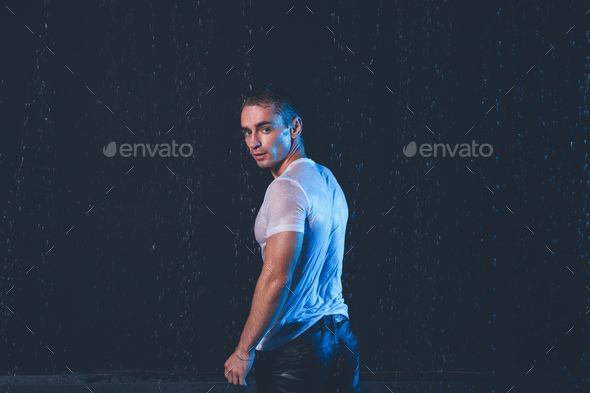 Fresh portrait of muscular man with water splashes on dark background. - Stock Photo - Images