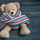 Cute teddy bear with colorful scarf sitting on blue wooden background - PhotoDune Item for Sale