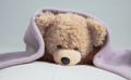 Cute teddy laying on bed mattress covered with a towel - PhotoDune Item for Sale