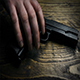 Hand Picks Up Gun Off Table Moving Shot - VideoHive Item for Sale