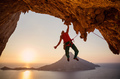 Male rock climber hanging on cliff with one hand at sunset - PhotoDune Item for Sale