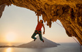 Male rock climber hanging with one hand on challenging route on cliff  - PhotoDune Item for Sale