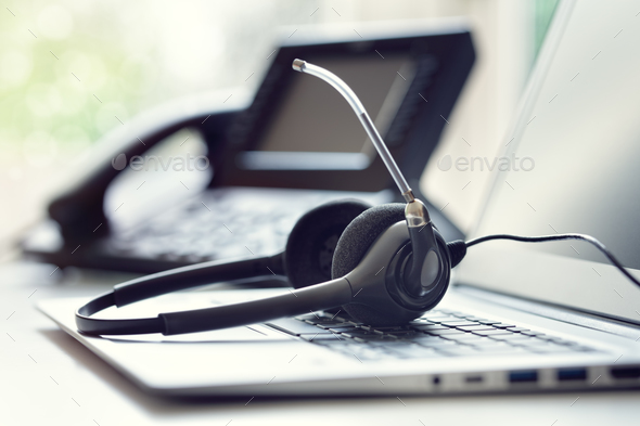 Headset headphones telephone and laptop in call center - Stock Photo - Images