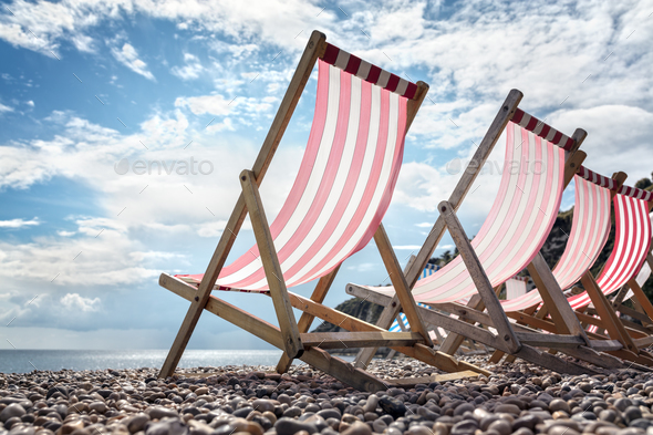 Deck chairs on the beach at the seaside summer vacation - Stock Photo - Images