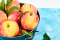 Ripe peaches in a bowl, basket on the blue table - PhotoDune Item for Sale