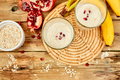 Smoothie with oat or oatmeal, banana and pomegranate on wooden rustic background - PhotoDune Item for Sale