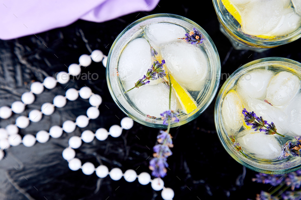 Lavender lemonade with lemon and ice on black background - Stock Photo - Images