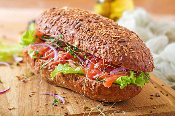Salmon sandwich - smorrebrod with cheese cream and microgreen on wooden table. - Stock Photo - Images