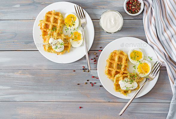 Healthy breakfast or snack. Potato waffles and boiled egg on grey wooden table. Top view. Flat lay - Stock Photo - Images