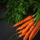 Bunch of fresh carrots with green leaves on  dark  background. Flat lay. Top view - PhotoDune Item for Sale