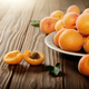 Clay dish full of ripe apricots on wooden table - PhotoDune Item for Sale
