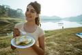 a woman enjoy happy breakfast in side lake - PhotoDune Item for Sale
