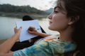 close up caucasian woman alone sitting side lake and writing not - PhotoDune Item for Sale