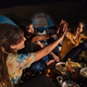 group of friends giving high five while sitting around campfire - PhotoDune Item for Sale