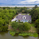 Free Download Aerial view of waterfront home on wooded property Nulled