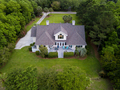 Aerial view of large home with new roof on wooded grassy propert - PhotoDune Item for Sale
