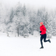 Woman running on snow in winter mountains - PhotoDune Item for Sale