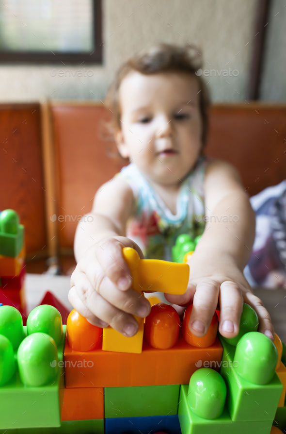 Little girl playing with toy blocks - Stock Photo - Images